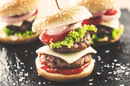 Mini double burgers appetizer, vintage look food. Stock Photo