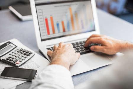 calculadora: De negocios que trabaja en su computadora port�til en una oficina moderna.
