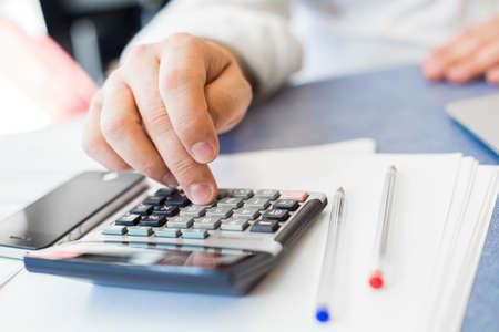 reckon: Man hand with calculator at workplace office.