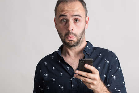 suprise: Portrait of man holding a phone with suprise expression.