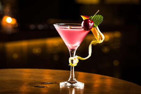 Pink cocktail with cherry and mango in a club.