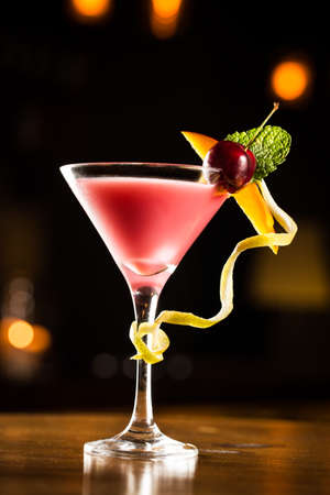 bar drinks: Pink cocktail with cherry and mango in a club.
