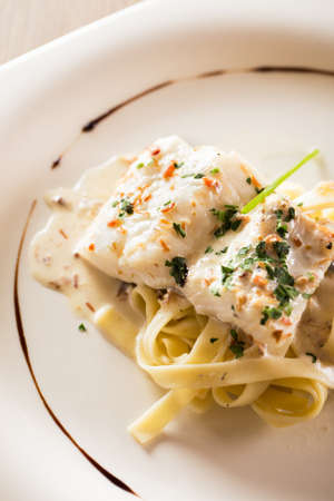 hake: Cooked hake with sauce and pasta.