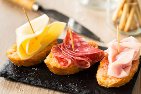 antipasto: Antipasto food with cheese, salami, and tork ham with breadsticks.