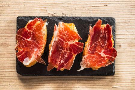Jamon iberico, las mejores tapas de jamón español. Vista superior de una mesa de madera. Foto de archivo - 45593702