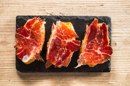 tapas: Jamon iberico, the best spanish ham tapas. Top view on a wooden table. Stock Photo