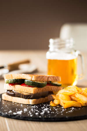 copy sapce: Vegetables sandwich with glass of beer on a wood table. Vertical copy space.