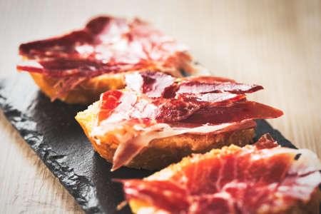 Jamon iberico, the best spanish ham tapas. Vintage food edition. Archivio Fotografico