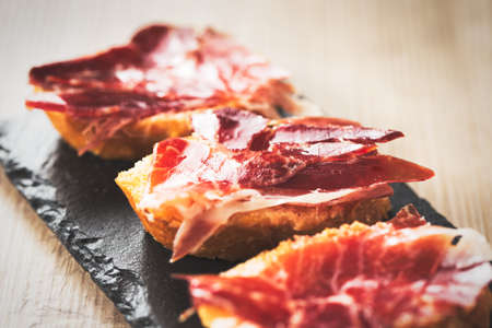 serrano: Jamon iberico, the best spanish ham tapas. Vintage food edition. Stock Photo