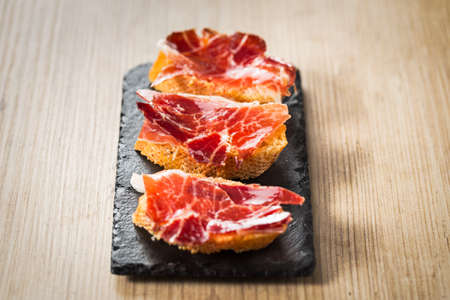 catering food: Jamon iberico, the best spanish ham tapas on a wood table.