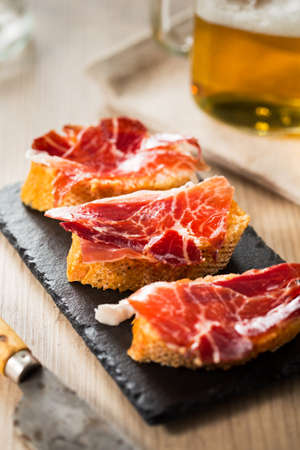 Jamon iberico, the best spanish ham tapas on a slice of bread and beer. Stock Photo