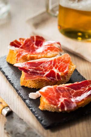 iberico: Jamon iberico, the best spanish ham tapas on a slice of bread and beer. Stock Photo