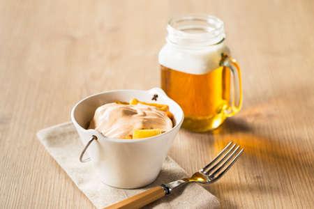 tarro cerveza: Patatas típicas bravas con jarra de cerveza en una mesa de madera.