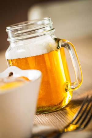 tarro cerveza: Gran tarro de cerveza en una mesa de madera. Foto de archivo