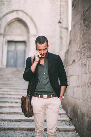 horizontal haircut: Portrait of young bearded man talking on his phone while standing on steps of city building
