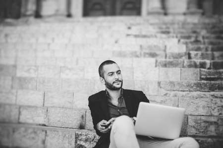 horizontal haircut: Portrait of young bearded man using his laptop while sitting on steps of city building Stock Photo