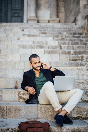 horizontal haircut: Portrait of young bearded man talking on his phone while sitting on steps of city building