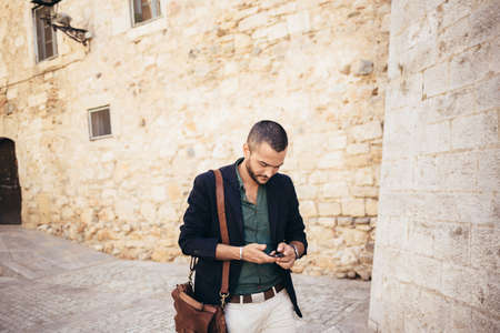 horizontal haircut: Portrait of young bearded man talking on his phone while walking in the street Stock Photo