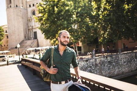 horizontal haircut: Handsome bearded man walking on bridge and looking away. Summertime Stock Photo
