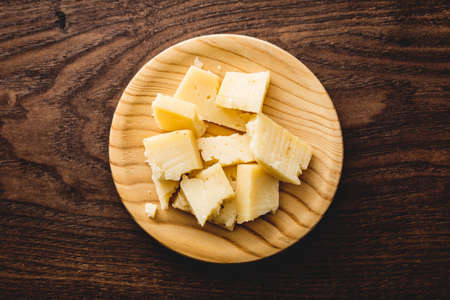 Delicious spanish cheese on a wood board, top view.