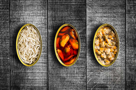 Three canned food above grunge wooden table. Top view. Stock Photo
