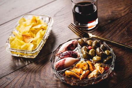 aperitivo español tradicional vermut con la bebida, comida enlatada y patatas fritas.