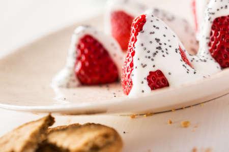 amapola: fresas frescas en un plato con semillas de amapola y yogur.