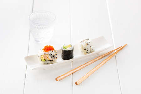 sake maki: Fresh and delicious maki sushi with sake glass and chopsticks on a wooden white table. Stock Photo