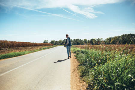 lonliness: Young traveller walking alone in rural scene.
