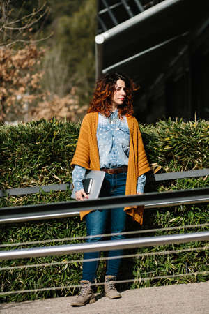 red haired woman: Smiling red haired woman with laptop standing near metal railings while looking away