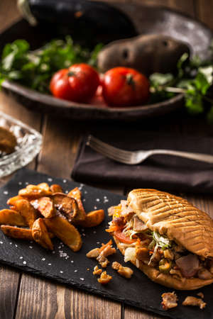 Doner kebab with fried potato on served wooden table Stock Photo