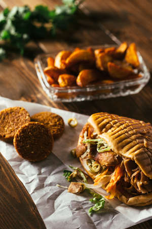 turkish kebab: Tasty chicken doner kebab with falafel on a wooden table Stock Photo