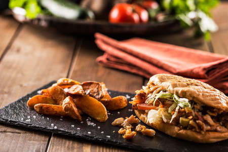 donner: Tasty chicken doner kebab with fried potato on a wooden table