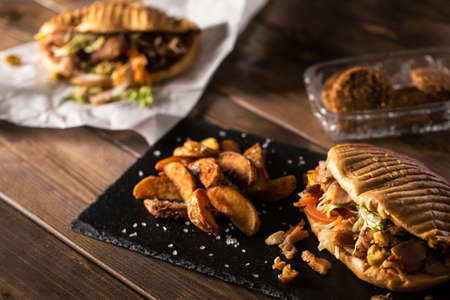 donner: Tasty chicken doner kebab with fried potato on a wooden table with falafel