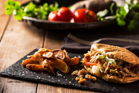 Doner kebab with fried potato on served wooden table