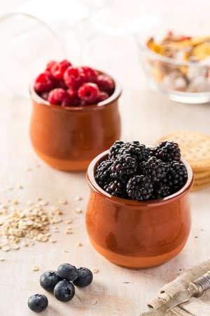 bilberries: Close-up of blackberries and raspberries on table in kitchen. Scattered bilberries.
