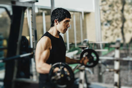 brunets: Muscular man doing exercise with dumbbells in gym Stock Photo