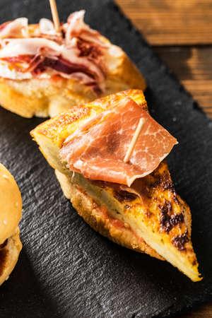hams: deliciosas tapas españolas y la cerveza servida en una mesa de madera.