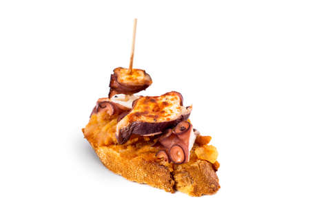 galician: Typical spanish food. Pincho with galician octopus on slice of bread. Isolated on white background. Stock Photo