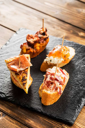 Delicious spanish tapas  served on a wooden table.