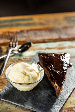 Delicious chocolate cake with vanilla ice cream on a wooden table.