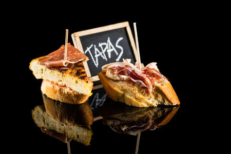 tapas espa�olas: Spanish tapas isolated on black background with chalkboard.