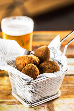 Traditional fried croquette with glass of beer on a wooden table.