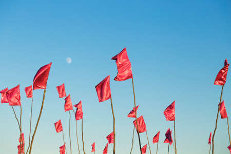 Waving red flags on bright blue sky waving in wind