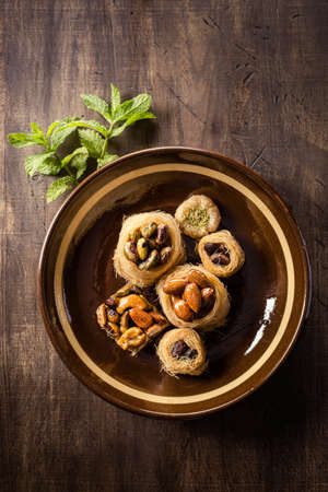sweettooth: Top view of delicious traditional arabic nests with nuts on brown plate with mint