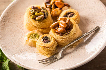 sweettooth: Close-up of yummy traditional syrian pastry served on plate with ornaments and silver fork