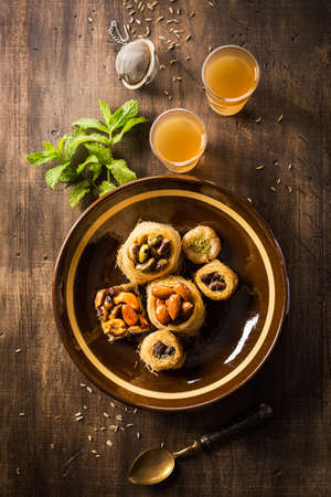 Above view of yummy syrian dessert on brown ceramic plate with mint and glasses of tea Stock Photo
