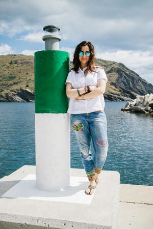 white pole: Portrait of casually clothed brunette woman with arms crossed leaning on green and white pole with light for vessels against of hilly land