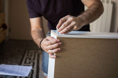 unrecognizable person: Close up of unrecognizable person tightens screw while assembling furniture indoor