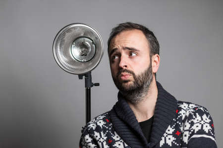 outstretched hand: Portrait of adult bearded man holding camera on outstretched hand taking selfie and shows thumb up against studio flashlight